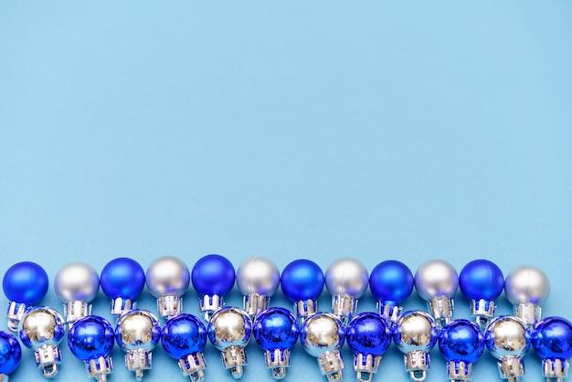 Nieuwjaarssamenstelling kerstballen van blauwe en zilveren kleur liggen op een rij op een blauwe achtergrondfla...