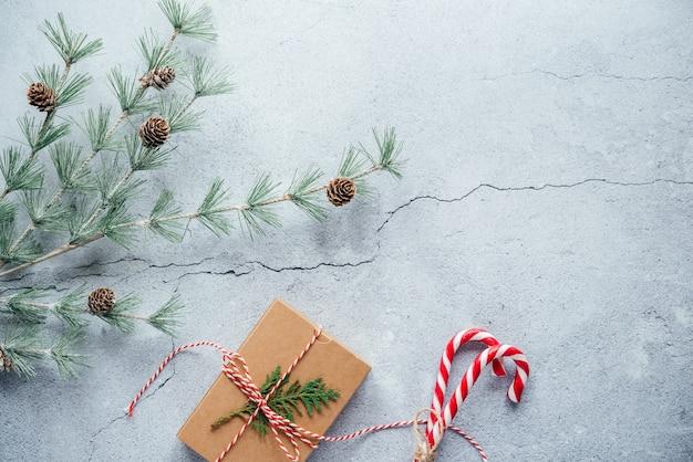 Nieuwjaarssamenstelling met kerstcadeaudoos, dennenappels en thuja-takken