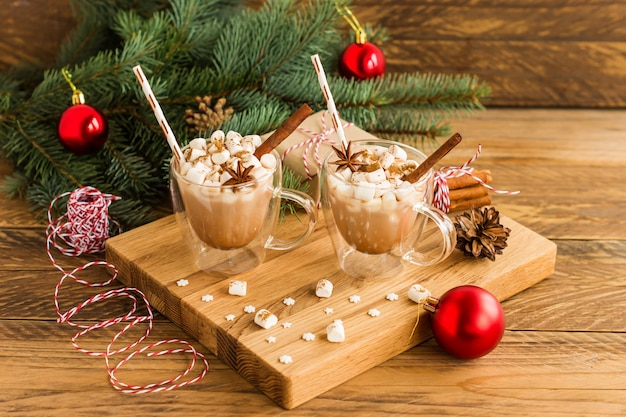 Nieuwjaarssamenstelling van twee mokken met warme chocolademelk en marshmallow op een houten ondergrond met een vuren tak en rode ballen.