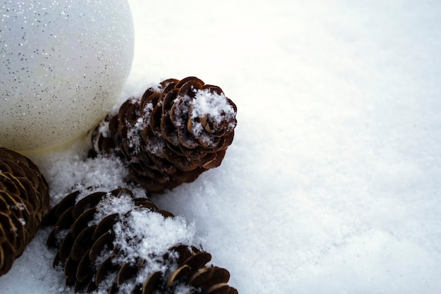 Nieuwjaarsspeelgoed en kegels liggen in de sneeuw