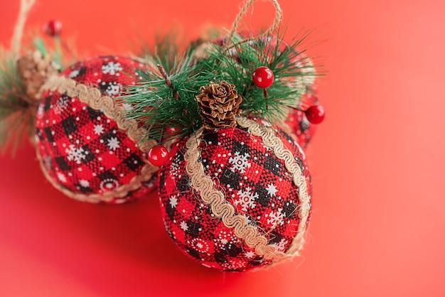 Nieuwjaarsspeelgoed gemaakt van stof versierd met een kerstboom op een rode achtergrond. kerstmis.