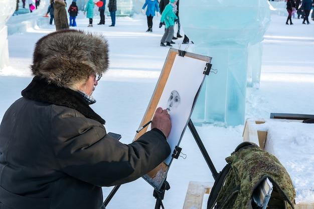 Nieuwjaarsspeeltuin met ijssculpturen. de kunstenaar tekent in de open lucht een portret met potlood.