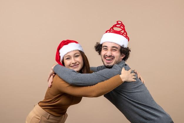 Nieuwjaarsstemming en feestconcept - jong opgewonden mooi paar dat kerstman-hoeden draagt die elkaar op grijze beelden omhelzen