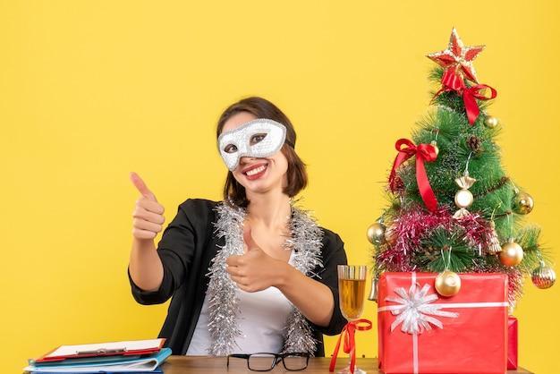 Nieuwjaarsstemming met charmante dame in pak die masker draagt dat ok gebaar op kantoor maakt