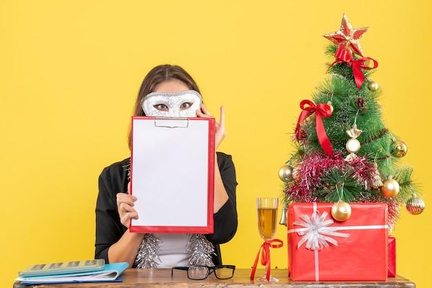 Nieuwjaarsstemming met charmante dame in pak die masker draagt en document in het bureau toont