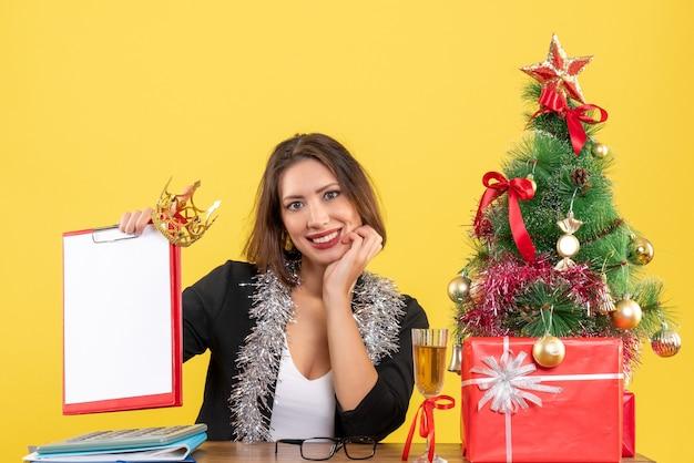 Nieuwjaarsstemming met charmante dame in pak met document en kroon op kantoor