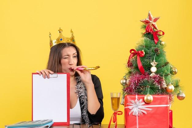 Nieuwjaarsstemming met doordachte charmante dame in pak met het document van de kroonholding in het bureau op geïsoleerd geel
