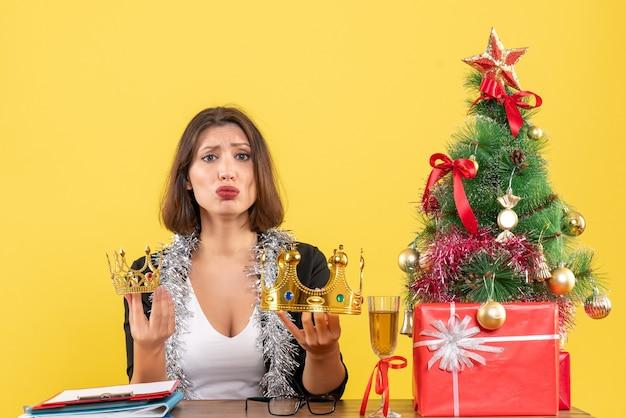 Nieuwjaarsstemming met doordachte charmante dame in pak met kronen in het kantoor op geel geïsoleerd