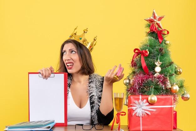 Nieuwjaarsstemming met doordachte verwarde charmante dame in pak met het document van de kroonholding in het bureau op geïsoleerd geel