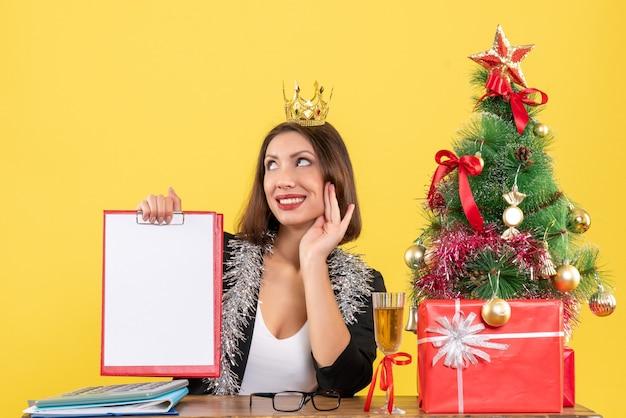 Nieuwjaarsstemming met dromerige charmante dame in pak met document van de kroonholding op kantoor