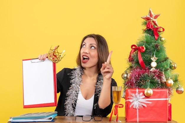 Nieuwjaarsstemming met geschokte charmante dame in het document en de kroon van de kostuumholding in het bureau op geïsoleerd geel