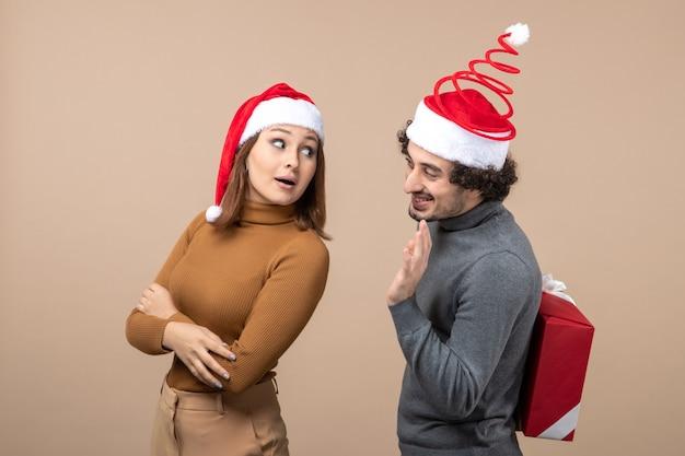 Nieuwjaarsstemming met grappig mooi paar dat rode kerstman-hoeden draagt die met elkaar op grijs spreken