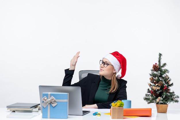 Nieuwjaarsstemming met jonge aantrekkelijke vrouw met een kerstman hoed zittend aan een tafel met een kerstboom en een cadeau erop en zegt hallo op kantoor