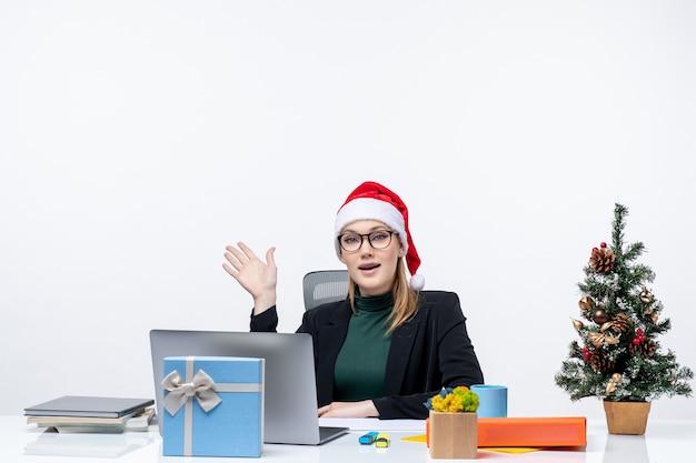 Nieuwjaarsstemming met jonge aantrekkelijke vrouw met een kerstman hoed zittend aan een tafel met een kerstboom en een cadeau erop praten over iets op kantoor