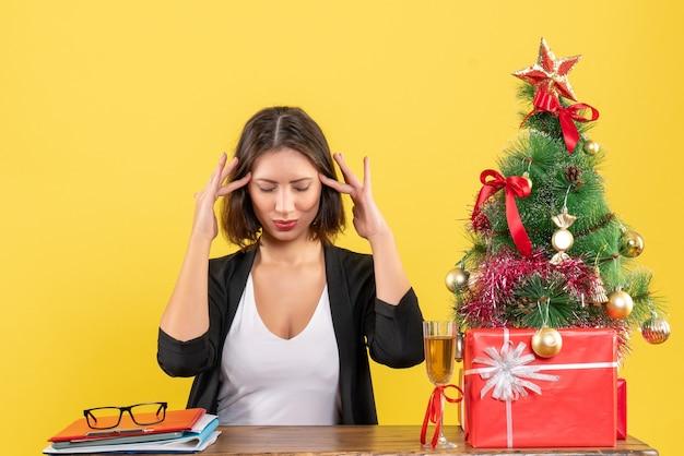 Nieuwjaarsstemming met jonge gelukkig emotionele zakelijke dame droomt van iets en zittend aan een tafel in het kantoor op geel