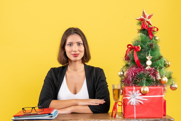 Nieuwjaarsstemming met jonge gelukkig emotionele zakelijke dame zittend aan een tafel in het kantoor op geel