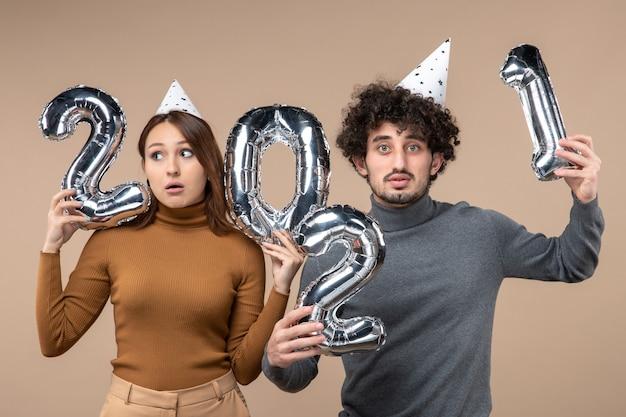 Nieuwjaarsstemming met jonge paar dragen nieuwe jaar hoed vormt voor camera meisje toont en en jongen met en op grijs