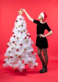 Nieuwjaarsstemming met jonge vrouw in zwarte kleding en kerstmanhoed die zich dichtbij witte kerstboom bevinden die ster erop schikken