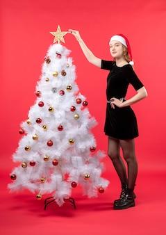 Nieuwjaarsstemming met jonge vrouw in zwarte kleding en kerstmanhoed die zich dichtbij witte kerstboom bevindt