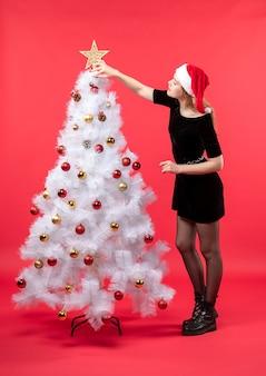 Nieuwjaarsstemming met jonge vrouw in zwarte kleding en kerstmanhoed die zich dichtbij witte ster van de kerstboomholding bevinden