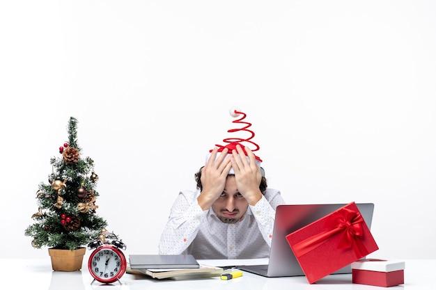 Nieuwjaarsstemming met jonge zakenman met grappige kerstman-hoed die uitgeput voelt van alles op kantoor op witte achtergrond