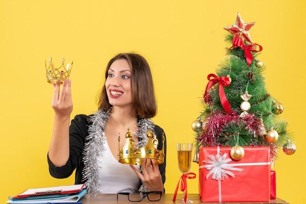 Nieuwjaarsstemming met lachende charmante dame in pak met kronen in het kantoor op geel geïsoleerd