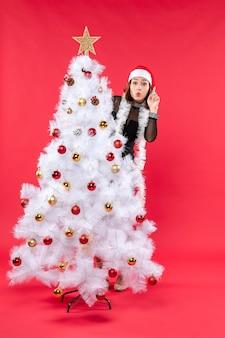Nieuwjaarsstemming met mooi meisje in een zwarte jurk met kerstman hoed achter de kerstboom