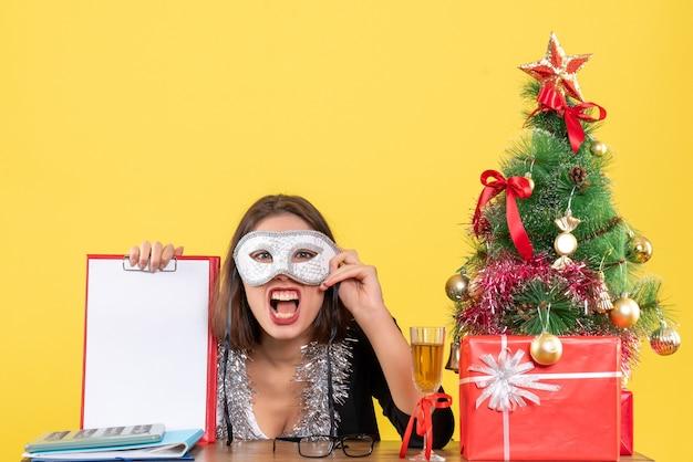 Nieuwjaarsstemming met nerveuze charmante dame in pak die masker draagt en document in het bureau op geïsoleerd geel toont