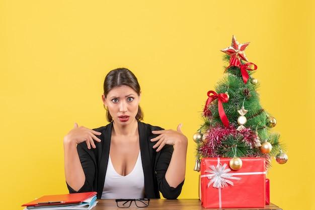 Nieuwjaarsstemming met nieuwsgierige jonge vrouw in pak met versierde kerstboom op kantoor