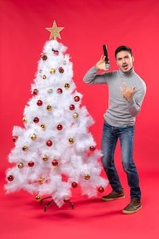 Nieuwjaarsstemming met positieve kerel die hiphoplied zingt dat zich dichtbij versierde kerstboom op rood bevindt