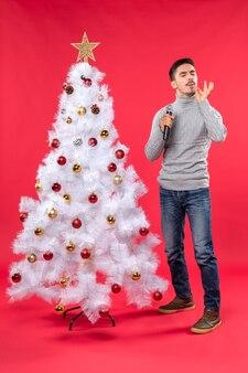 Nieuwjaarsstemming met positieve kerel gekleed in spijkerbroek die zich dichtbij versierde kerstboom bevindt