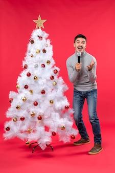 Nieuwjaarsstemming met positieve man zingen lied staande in de buurt van versierde kerstboom op rode beelden