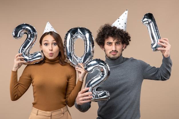 Nieuwjaarsstemming met slimme jonge paar dragen nieuwe jaar hoed vormt voor de camera meisje toont en en jongen
