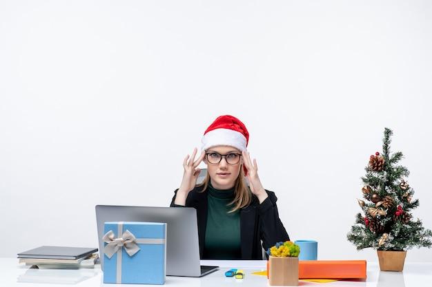 Nieuwjaarsstemming met vastberaden vrouw met een kerstman-hoed zittend aan een tafel met een kerstboom en een cadeau erop op een witte achtergrond