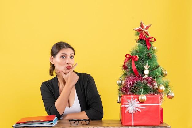 Nieuwjaarsstemming met verrast jonge vrouw in pak met versierde kerstboom op kantoor op geel