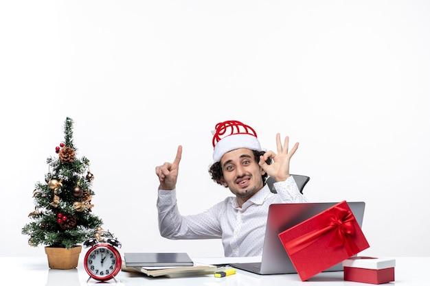 Nieuwjaarsstemming met verrast lachende opgewonden jonge zakenman zitten in het kantoor en perfect gebaar maken op witte achtergrond