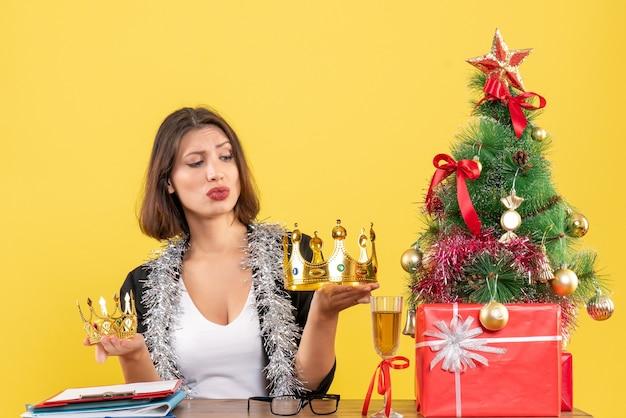 Nieuwjaarsstemming met verwarde charmante dame in pak met kronen op kantoor