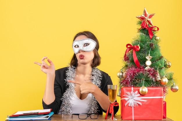 Nieuwjaarsstemming met verwarde charmante dame in pak met masker op kantoor