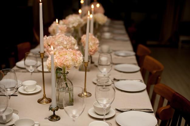 Nieuwjaarstafel geserveerd voor een feestelijk diner. kerst instelling op houten tafel met decoratie platen en wijnglazen en rode kaarsen op grijs wazig bokeh achtergrond