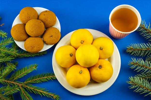 Nieuwjaarstafel voor kinderen met koekjes, limonade en mandarijnen.