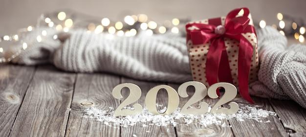 Nieuwjaarstilleven met decoratief nummer van het komende jaar met decordetails op onscherpe achtergrond.