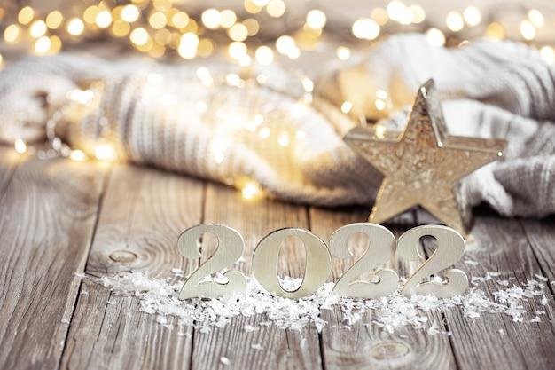 Nieuwjaarstilleven met decoratief nummer van het komende jaar op een houten ondergrond tegen een onscherpe achtergrond.