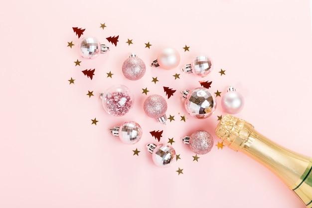 Nieuwjaarsvakantie met fles champagne op roze achtergrond. kerstmis, nieuwjaar. feestelijk plat leggen, bovenaanzicht, kopieerruimte