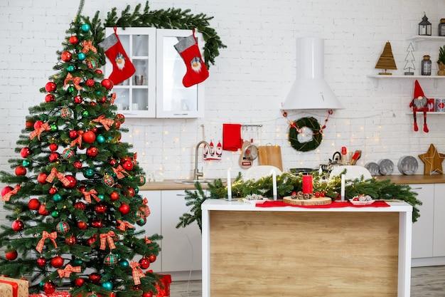 Nieuwjaarsversieringen in de keuken: een groene boom versierd met rode en groene ballen, nieuwjaarsversieringen, gele slingers. nieuwjaar. het huis versieren voor kerst