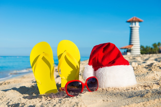 Nieuwjaarsviering aan de kust. kerstmuts, sandalen, zonnebrillen - kerstvakantie op zee.