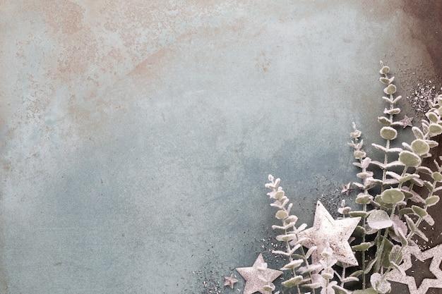 Nieuwjaarsviering en kerstmis achtergrond met gouden bloemen, sneeuw, sterren en kerstversiering bovenaanzicht.