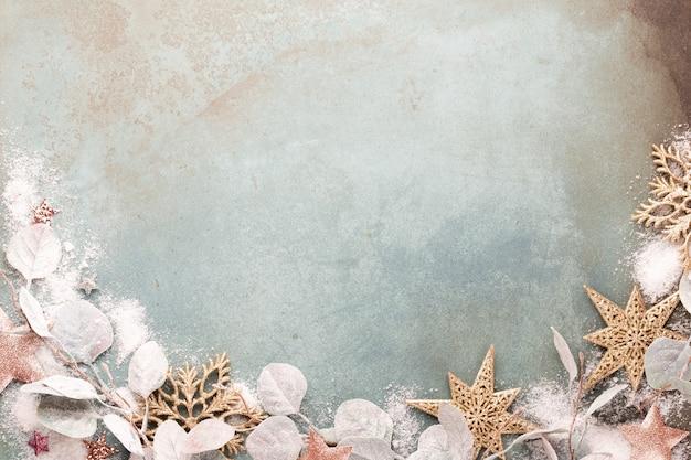 Nieuwjaarsviering en kerstmis achtergrond met roze bloemen, sneeuw, sterren en kerstversiering bovenaanzicht.