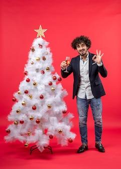 Nieuwjaarsviering met bebaarde jonge man die een glas wijn houdt die brillengebaar maakt