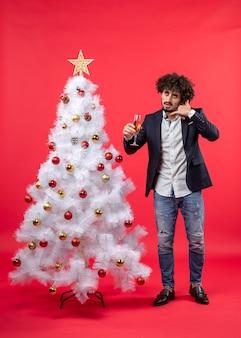 Nieuwjaarsviering met bebaarde jonge man met een glas wijn en bel me gebaar