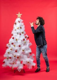 Nieuwjaarsviering met bebaarde jongeman wijn drinken en permanent in de buurt van versierde witte kerstboom